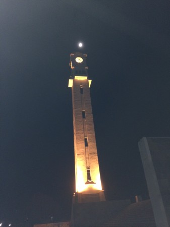The clock tower on campus with the moon shining above